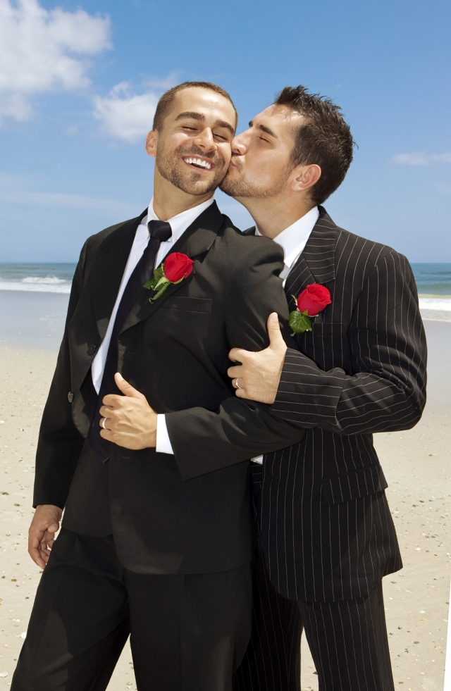 Two gay grooms kissing.  Men in suits.