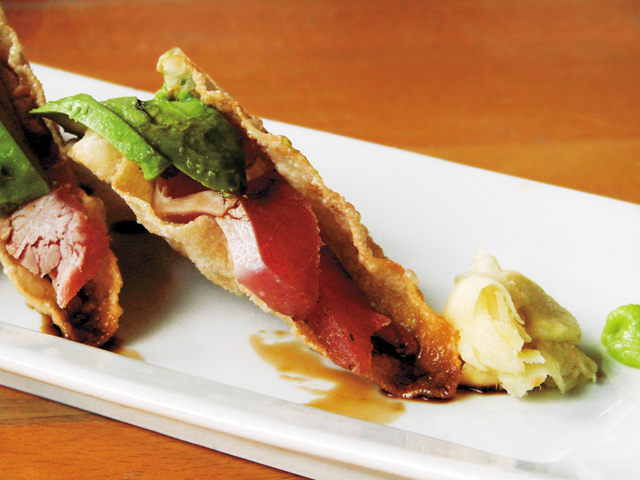 Tuna Tacos feature thick slabs of tuna with avocado and salty sauce in crispy casing.