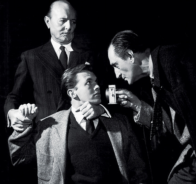 Kilburn,  (Walker), is interrogated by Jack Raines (Watson, L) and Basil Rathbone (Sherlock Holmes, R).  Written by Rathbone's wife, Ouida, Sherlock Holmes ran on Broadway for three performances in the New Century Theatre, October 30-31, 1953.