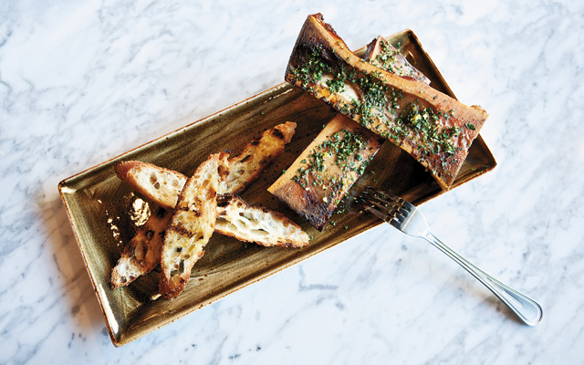 "Good to the bone: Adventurous ""foodies"" can't miss the Bone Marrow. Huge cow bones with their marrow are a smokey surprise, covered in a gremolata of parsley, garlic, lemon zest, and salt.  Smear it on toasted bread and share! Photo by Hubert Bonnet"
