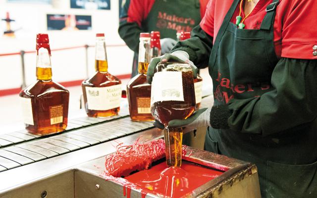 Dipping the famous bourbon bottles. Photo courtesy of Maker's Mark Distillery
