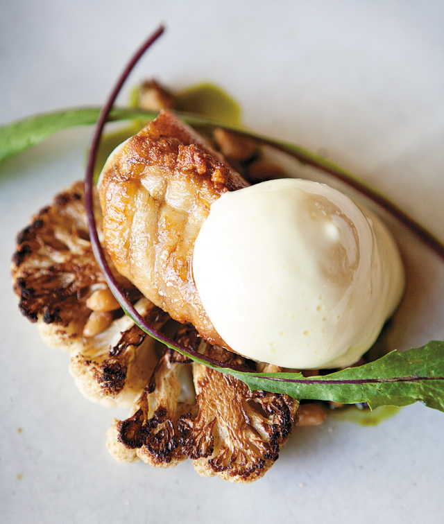 Monkfish Roasted on the bone with pine nuts steeped in vinegar and partially topped with carmelized yogurt. Served with thinly sliced, roasted cauliflower. Photo by Hubert Bonnet