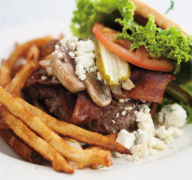 A hand-pattied Mushroom Bacon Bleu Burger with a side of fresh, hand-cut fries. Photo by Hubert Bonnet