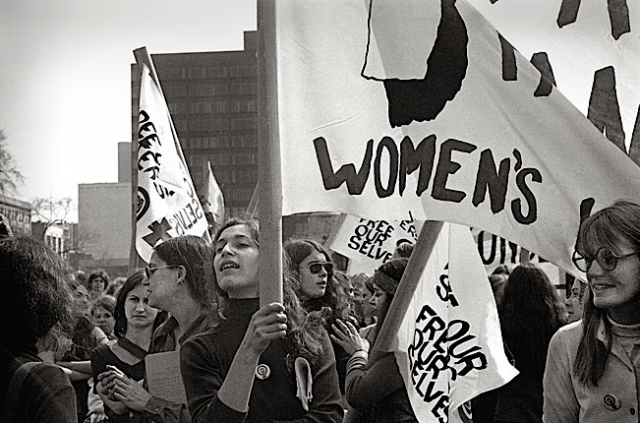 """""""Woman with banner"""". Photo by Virginia Blaisdell."""