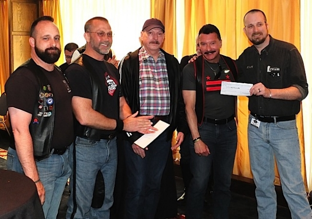 Members of the Centaur Motorcycle Club present a $6,000 check to Rick Storer (right), Executive Director of the Leather Archives & Museum in Chicago. Photo by Steve Lenius.