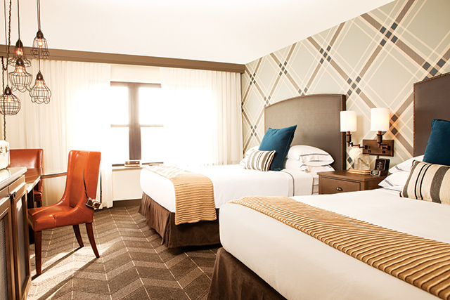 The geek-chic style of the hotel is ever-present in the guest rooms with a blue plaid accent wall. Photo courtesy of The Commons Hotel