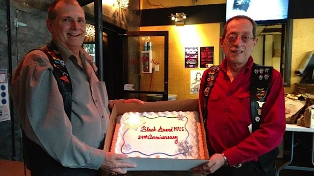 Black Guard members Thomas Weiland, left and Michael Delorme, right, display the Black Guard 39th-anniversary cake. Photo courtesy of the Black Guard.