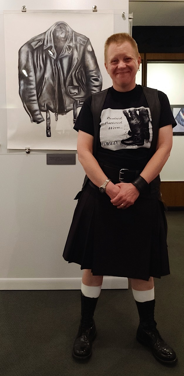 """Artist and bootblack Leslie J. Anderson stands in front of """"Forever Leather,"""" a work of art that was created using boot and shoe polish. Anderson is wearing one of her limited-edition T-shirts. Photo by Steve Lenius."""