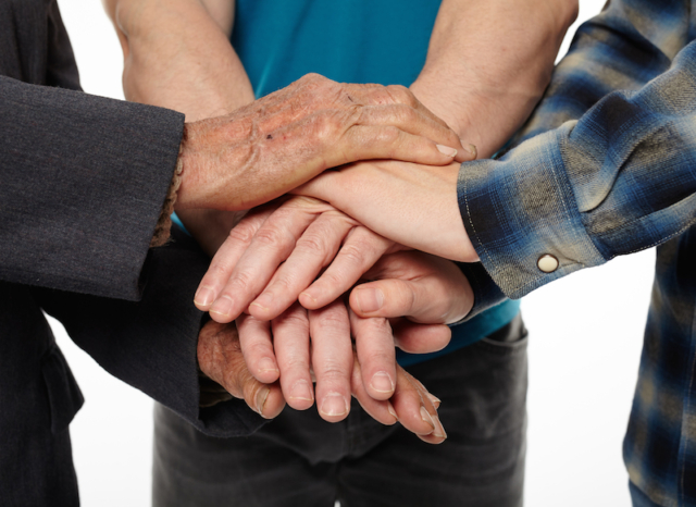 Three generations - grandfather son and grandson holding hands giving help and support each other