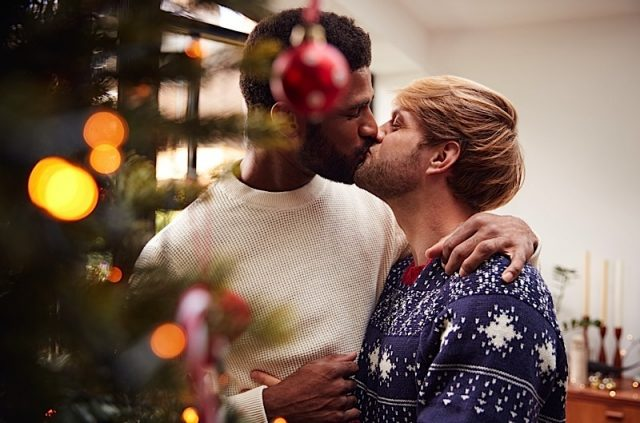 Gay Male Couple Kissing As They Hang Decorations On Christmas Tree At Home Together