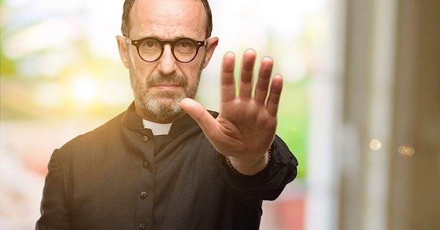 Priest religion man annoyed with bad attitude making stop sign with hand, saying no, expressing security, defense or restriction, maybe pushing