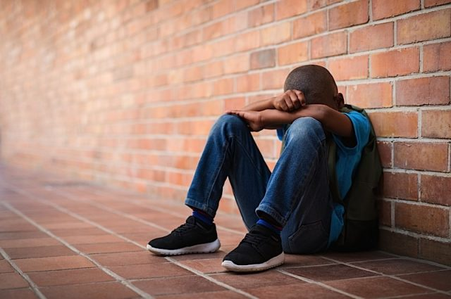 Young boy sitting alone with sad feeling at school. Depressed african child abandoned in a corridor and leaning against brick wall. Bullying, discrimination and racism concept with copy space.