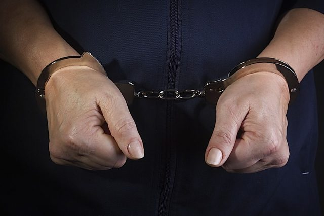 Prisoner woman with handcuffs in her arms