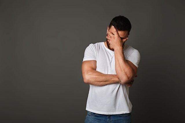 Young man with facepalm gesture. Disappointed stressed guy in white t-shirt covering face with hand on studio background, copy space