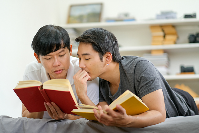 Asian Gay Couple Read Some Books Together In The Reading Room Of