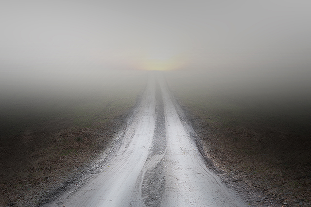 small rural dirt road leading into thick fog