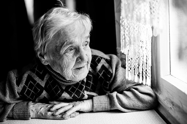 An old woman looking at the window. Black and white photo.