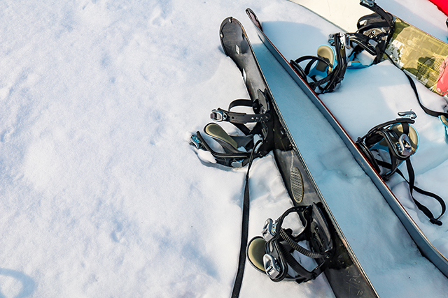 Hokkaido, Japan - December 2019 : Pair of Ski and snowboard equipment ready to use with background on snow in ski area. Skis in snow in winter season on the top mountains in Kiroro ski resort.