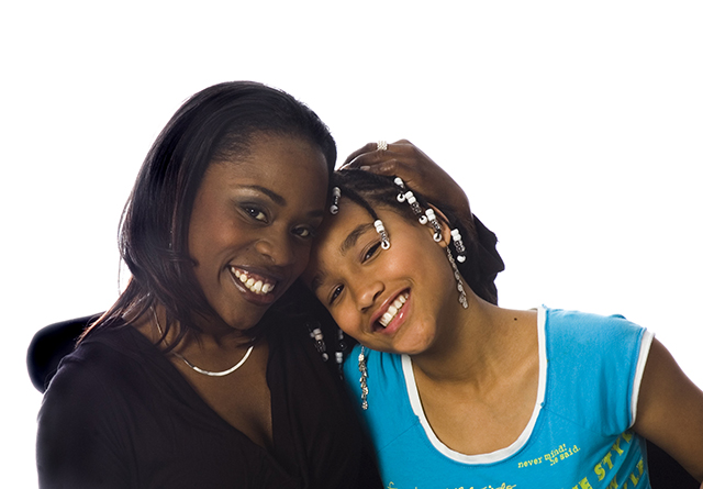 African american mother and daughter hugging and smiling on a white background