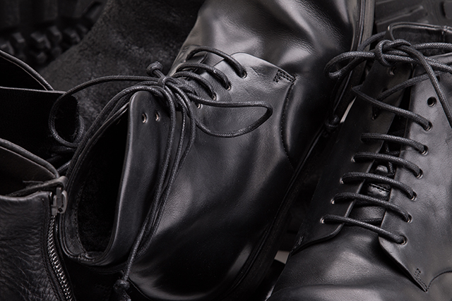 Genuine leather boots close up. Lots of fashionable shoes close up. High boots in black leather.