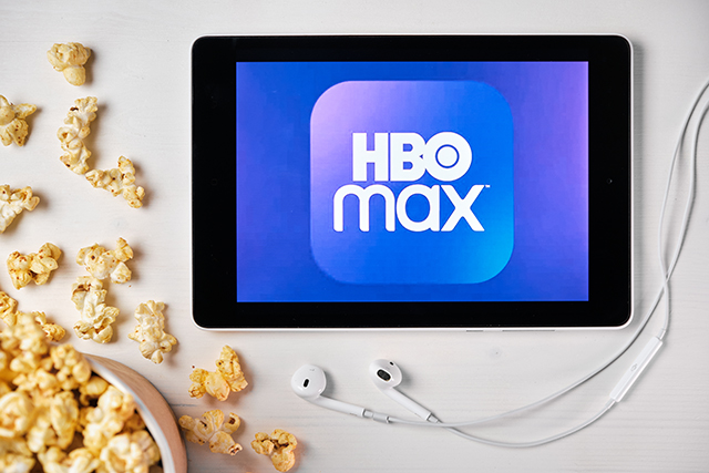 HBO max logo on the tablet screen laying on the white table with scattered popcorn and Apple earphones. Spending free time at home or news advertisement, September 2020, San Francisco, USA.