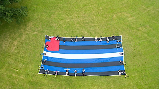 The 2020 version of the traditional community photo with the giant Leather Pride flag—this time, an aerial photo created using a drone. Photo by Larry Barthel.