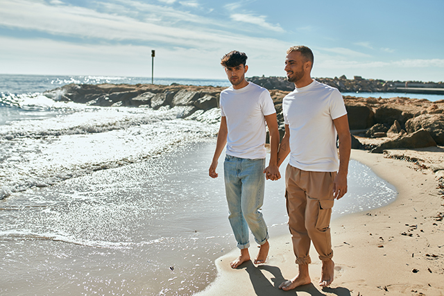 Young gay couple smiling happy walking at the beach.