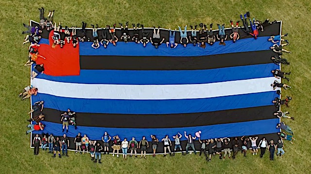 June 26, 2021: A photo from the 2021 community photo shoot with the giant Leather Pride flag. Photo by Larry Barthel