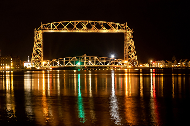 The iconic Duluth Minnesota Aerial Lift Bridge with reflections on calm harbor waters at night. Photo courtesy of BigStock/scandamerican